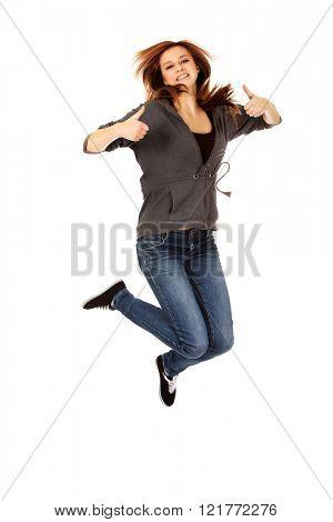 Teenage woman jumping showing thumbs up