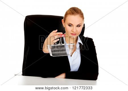 Smile business woman holding shopping cart and sitting behind the desk