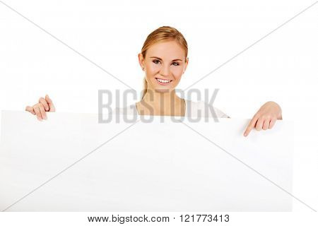 Smiling young woman pointing for empty banner