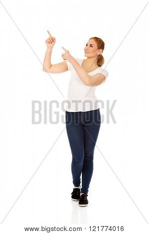 Young happy woman pointing for copyspace or something