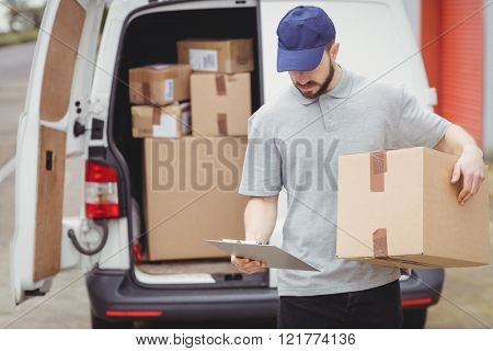 Delivery man reading notes on his clipboard while holding package