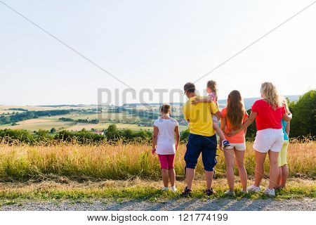 Family having walk looking at the landscape of their home on a summer evening