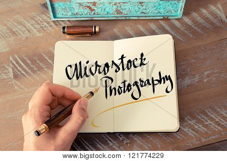 Retro effect and toned image of a woman hand writing a note with a fountain pen on a notebook. Handwritten text Microstock Photography as business concept image