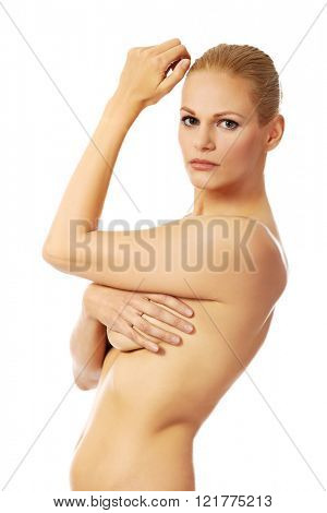 Side view of topless woman covering her breast