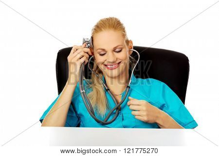 Funny female doctor or nurse sitting behind the desk with stethoscope