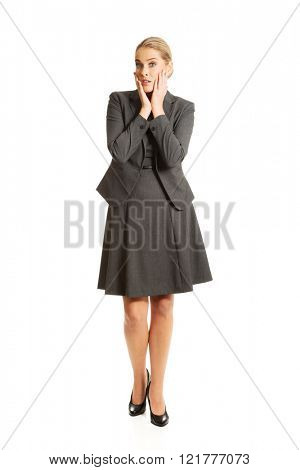 Amazed businesswoman holding hands on chin