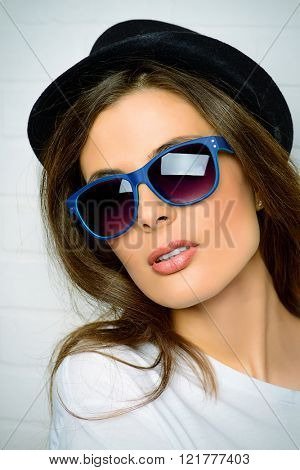 Modern young woman in sunglasses and a hat standing by a brick wall.
