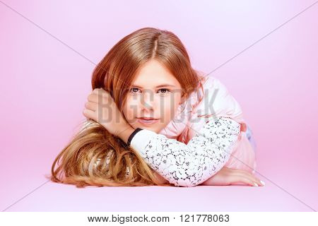 Smiling girl teenager with beautiful healthy long hair lying on a floor over pink background. Studio shot.
