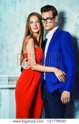 Gorgeous couple of young people stand in a room with vintage interior. Fashion shot.