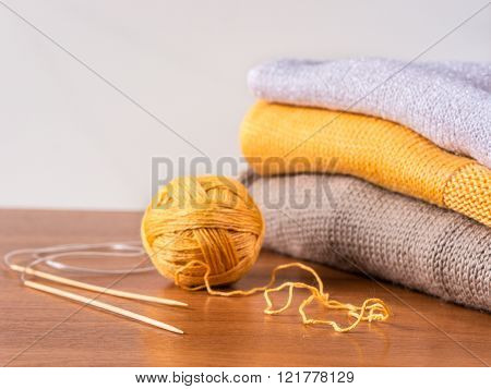 yarn, needles and knitwear on wooden table