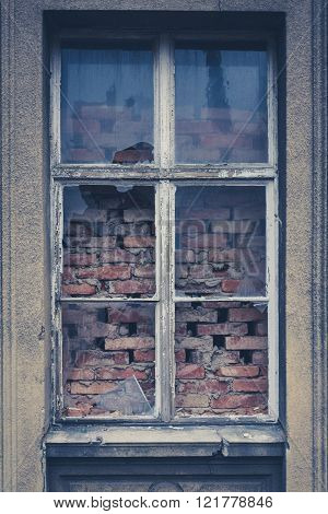 old shattered window, broken glass, bricked window