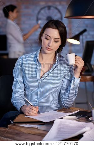 Young businesswoman sitting at desk, writing, drinking coffee.
