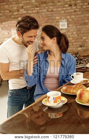 Loving couple having breakfast together at home.
