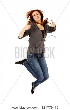 Teenage woman jumping showing thumbs up