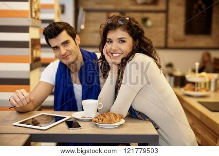 Portrait of attractive young couple in cafeteria, smiling happy, looking at camera.