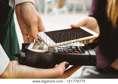 Woman paying with mobile phone in cafe