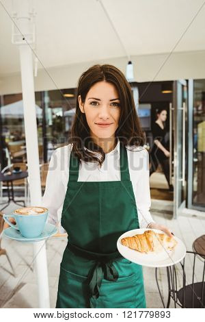 Waitress posing with coffee and croissant in cafe