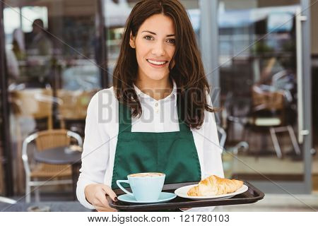 Waitress holding tray with coffee and croissant in cafe