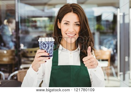 Smiling waitress serving a coffee in cafe
