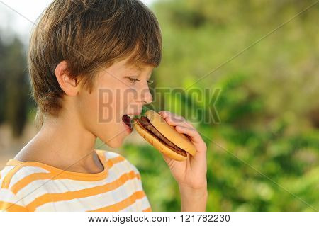 Young teenager boy eating tasty hamburger outdoors at green nature background