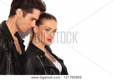 side view of sexy young couple in leather jackets looking away from the camera