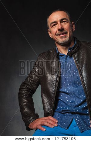 cut portrait of seated mature man in leather jacket resting hands while looking away from the camera in gray studio background