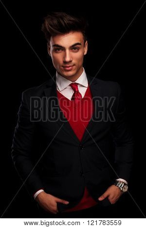 portrait of attractive male model in black suit and red tie, posing looking at the camera with hands in pockets in dark studio background