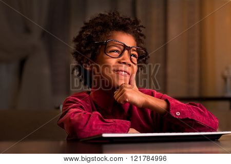Afro kid at keyboard smiling.