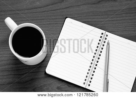 top view on opened notebook pen and cup of coffee
