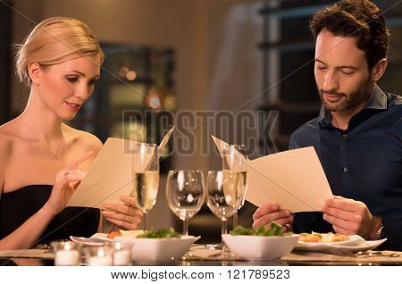 Young couple reading menu and choosing meal. Couple reading a card in restaurant while having dinner. Couple looking for dessert options in restaurant menu card.