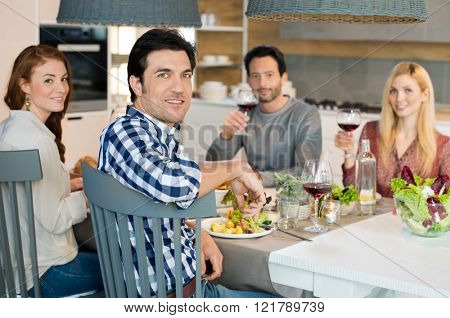 Group of friends eating at home. Portrait of happy young friends eating and drinking wine glass together. Smiling young friends having lunch together and looking at camera.