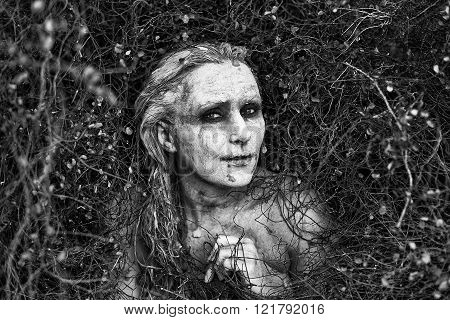 Freaky Woman with face covered in clay staring at the camera
