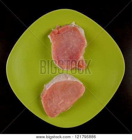 two pieces of raw pork meat on a green plate isolated black top view