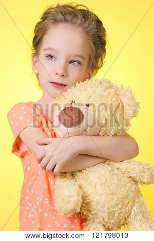 Portrait of beautiful girl 6 years which hugs a Teddy bear - isolated on yellow background