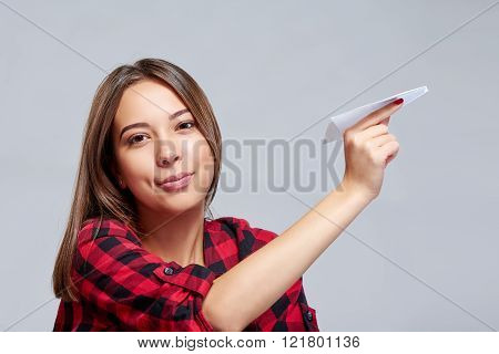 Dreamy female holding white paper plane