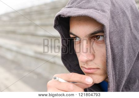 Young Man In Depression Smoking A Cigarette On A Stadion. Concept Of Young People With Harmful Habit