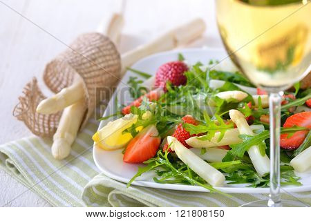 Colorful spring salad with fresh white aparagus, rocket salad and strawberries, served with a glass of dry and fruity white wine