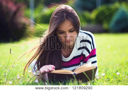 Young woman reading book in city park at summer day