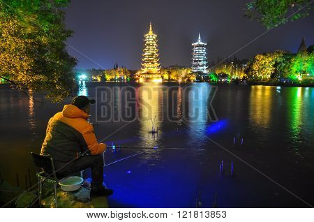 Night Fisherman On The Background Of The Sun And Moon Pagodas