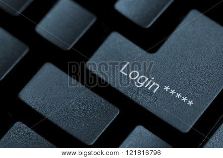 Horizontal close up of black keys on a keyboard with the word login on one of them