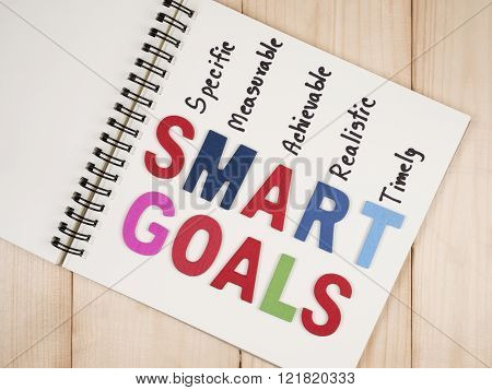 SMART Goals on blank notebook with wood background (Business Concept)