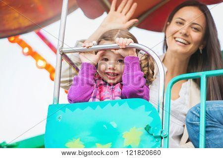 Mother and daughter enjoying fun fair ride, amusement park