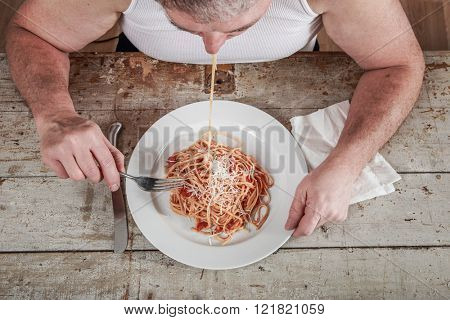 Man wearing an undershirt eating spaghetti, overeating adult.