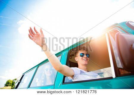 Teenage boys and girls inside an old campervan, roadtrip