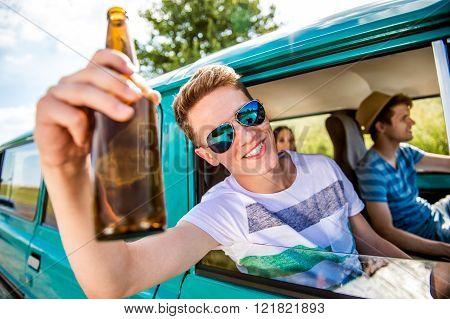 Teenagers inside an old campervan, drinking beer, roadtrip