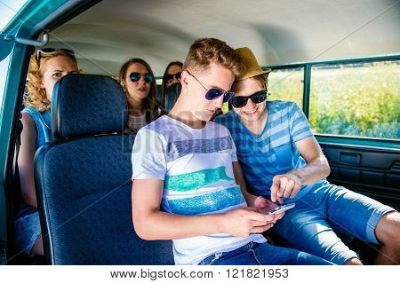 Teenagers with smartphone inside an old campervan, roadtrip
