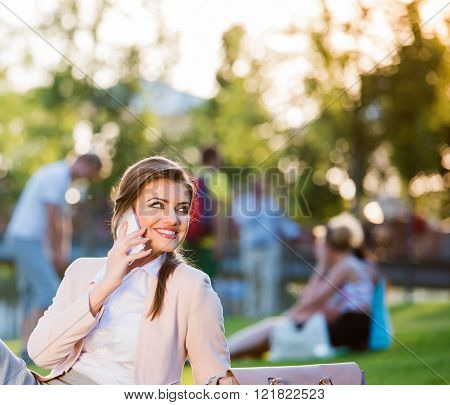 Businesswoman sitting in park, making a phone call, sunny day