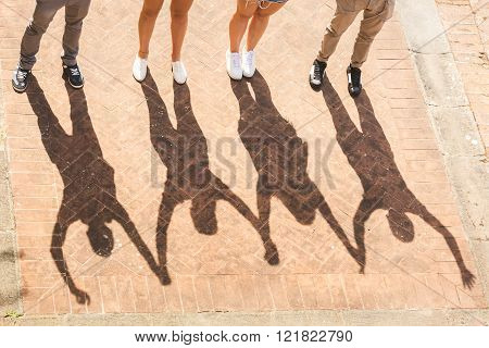 Shadows Of Friends Holding And Raising Hands  Together