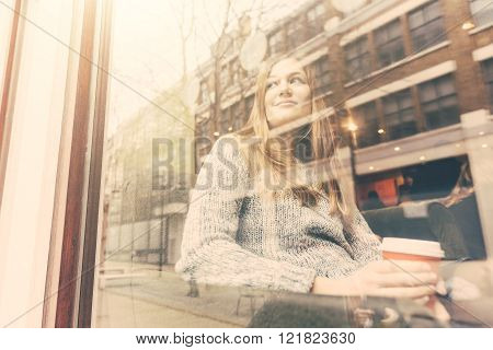 Beautiful Woman In A Cafe Seen Through The Window