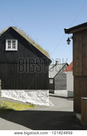 Traditional black wood and stone house with turf covered roof on the Faroe island.